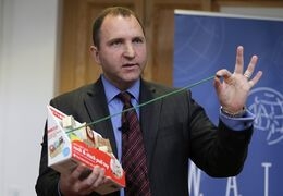 James Swartz, director of World Against Toys Causing Harm Inc., holds up a string on a children's pull toy at Children's Franciscan Hospital in Boston, Wednesday, Nov. 19, 2014. The consumer watchdog group has released its annual list of what it considers to be the 10 most unsafe toys as the holiday season approaches. (AP Photo/Charles Krupa)