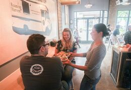 This June 20, 2014 photo shows Lance Hill, from left, and Chelsea Hill, both of Traverse City, being served by Rebecca Brown, co-owner, at Harvest in downtown Traverse City, Mich. Harvest is a new restaurant tucked into an alley off Front Street, the main drag a block from the bayshore. It's the brainchild of co-owner Simon Joseph, an entrepreneurial chef who cruised into town three years ago aboard Roaming Harvest, the city's first food truck. (AP Photo/ Traverse City Record-Eagle, Keith King)