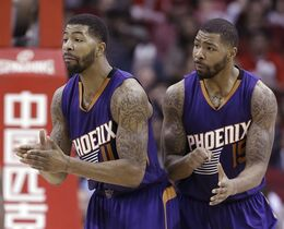 FILE - In this Dec. 6, 2014, file photo, Phoenix Suns' Markieff Morris (11) and Marcus Morris (15) talk to a referee during the second half of an NBA basketball game against the Houston Rockets in Houston. A Maricopa County grand jury has indicted the twins on felony aggravated assault charges. Court documents released Tuesday, April 21, 2015, show the brothers are accused of joining three other men in beating a man on Jan. 24, 2015, at a Phoenix recreation center. The names of the other men are redacted in the documents. (AP Photo/Pat Sullivan, File)