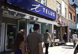 Pedestrians walk by a Telus store on Bloor Street West in Toronto on August 15, 2013. Mobilicity says it has agreed to be purchased by Telus Corp. (TSX:T) for $350 million. THE CANADIAN PRESS/Galit Rodan