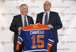 Edmonton Oilers CEO Bob Nicholson, left, and new President and General Manager Peter Chiarelli hold up an Oilers jersey with Chiarelli's name on it during a press conference in Edmonton, Alta., on Friday April 24, 2015. THE CANADIAN PRESS/Jason Franson