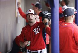 Washington Nationals starting pitcher Max Scherzer is high-fived by teammates in the dugout after throwing in the second inning of an exhibition spring training baseball game against the New York Mets, Thursday, March 5, 2015, in Viera, Fla. (AP Photo/David Goldman)