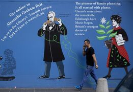 A man talking on a phone walks past images of Scots inventor Alexander Graham Bell and Scots doctor Marie Stopes outside the National Library of Scotland in Edinburgh, Scotland, Tuesday, Sept. 16, 2014. The land that gave the world haggis and tartan has produced so much more, from golf and television to Dolly the Sheep and