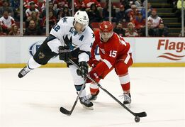 Detroit Red Wings center Riley Sheahan (15) defends San Jose Sharks center Patrick Marleau (12) during the first period of an NHL hockey game in Detroit on Thursday, March 26, 2015. (AP Photo/Paul Sancya)