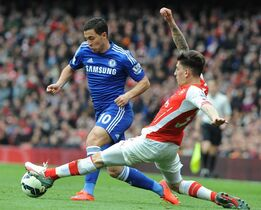 Arsenal's Hector Bellerin, right, tackles Chelsea's Eden Hazard during the English Premier League soccer match between Arsenal and Chelsea at the Emirates Stadium, London, England, Sunday, April 26, 2015. (AP Photo/Rui Vieira)