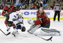 San Jose Sharks left wing Barclay Goodrow (89) dives for the puck in front of Minnesota Wild center Mikko Koivu, left, of Finland, as Wild goalie Darcy Kuemper, right, defends without his stick during the second period of an NHL hockey game in St. Paul, Minn., Tuesday, Jan. 6, 2015. The Wild have assigned Kuemper to their AHL affiliate for a conditioning assignment. THE CANADIAN PRESS/AP/Ann Heisenfelt
