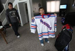 Daimon Gardner, 9, shows off his hockey jersey in his home in Warroad, Minn., as his father Vince looks on.