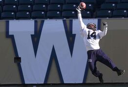 Winnipeg Blue Bomber Aaron Woods tries to complete a difficult pass during practice Thursday afternoon at Investors Group Field.