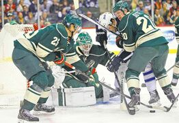 The Wild's Jonas Brodin (25), Ryan Suter (20) and Josh Harding (37) spar for the puck with the Jets' Eric Tangradi in front of the Wild's net Thursday.
