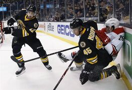 Boston Bruins' Joe Morrow (45) checks Carolina Hurricanes' Chris Terry (25) as the Bruins' Simon Gagne (12) clears the puck during the first period of an NHL hockey game in Boston, Saturday, Nov. 15, 2014. A person familiar with the decision has told The Associated Press that the Boston Bruins have placed veteran forward Simon Gagne on waivers for the purpose of releasing him. THE CANADIAN PRESS/AP/Michael Dwyer