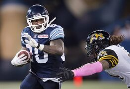 Toronto Argonauts' Steve Slaton, left, carries the ball past Hamilton Tiger-Cats' Taylor Reed during the second half of CFL action in Toronto, Ont. on Saturday, October 25, 2014. It's pretty simple for the Argonauts and Montreal Alouettes on Sunday: a win equals a ticket to the playoffs.THE CANADIAN PRESS/Darren Calabrese