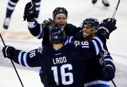 The Jets' Blake Wheeler (top) and Evander Kane (right) celebrate with Andrew Ladd after Ladd's shootout-winning goal Tuesday evening.
