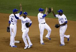 Kansas City Royals' Alcides Escobar (2), Jarrod Dyson, Omar Infante and Lorenzo Cain (6) celebrate after Game 2 of baseball's World Series against the San Francisco Giants Wednesday, Oct. 22, 2014, in Kansas City, Mo. The Royals won 7-2 to tie the series at 1-1. (AP Photo/Jeff Roberson)