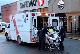 A man is loaded into an ambulance after a shooting incident in Surrey, B.C., Sunday, Dec.28, 2014. One man is dead following an officer-involved shooting that is now under investigation by the province's police watchdog. THE CANADIAN PRESS/Shane MacKichan