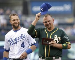 Oakland Athletics' Billy Butler, right, tips a Kansas City Royals cap belonging to former teammate Alex Gordon (4) after he was given his American League Championship ring before a baseball game Friday, April 17, 2015, in Kansas City, Mo. Butler was a member of the championship Royals last season before being traded to Oakland in the offseason. (AP Photo/Charlie Riedel)