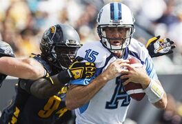 Toronto Argonauts quarterback Ricky Ray, right, is sacked by Hamilton Tiger-Cats defensive end Antonio Coleman during the second half of the annual CFL Labour Day Classic and inaugural game at the brand new Tim Hortons Field in Hamilton, Ont., Monday, September 1, 2014. THE CANADIAN PRESS/Aaron Lynett