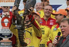 Driver Joey Logano holds the prize lobster as he celebrates in Victory Lane after winning the Sylvania 300 at New Hampshire Motor Speedway, Loudon, N.H., Sunday, Sept. 21, 2014 (AP Photo/Cheryl Senter)