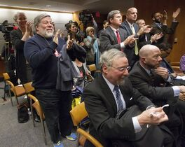Apple co-founder Steve Wozniak, left, stands up and joins others in the audience in applauding the Federal Communications Commission (FCC) vote on Net Neutrality during an open hearing at the FCC in Washington, Thursday, Feb. 26, 2015. The FCC has agreed to impose strict new regulations on Internet service providers like Comcast, Verizon and AT&T. The regulatory agency voted 3-2 Thursday in favor of rules aimed at enforcing what's called
