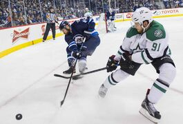 Winnipeg Jets Zach Bogosian (#44) fights for the puck against Dallas Stars Tyler Sequin (#91) Saturday January 31, 2015 at the MTS Centre during third period action.