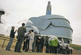 Visitors wait in the rain, with museum-supplied umbrellas, for their preview tours at the Canadian Museum for Human Rights on Saturday.