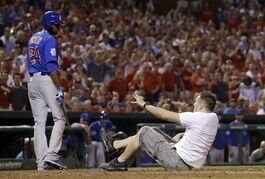 Chicago Cubs' Dexter Fowler, left, watches as a fan disrupts the game and flips over home plate during the sixth inning of a baseball game against the St. Louis Cardinals, Monday, May 4, 2015, in St. Louis. (AP Photo/Jeff Roberson)