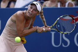 Caroline Wozniacki, of Denmark, gets her hair caught in her racket as she tries to return a shot to Aliaksandra Sasnovich, of Belarus, during the second round of the 2014 U.S. Open tennis tournament, Wednesday, Aug. 27, 2014, in New York. (AP Photo/Kathy Willens)