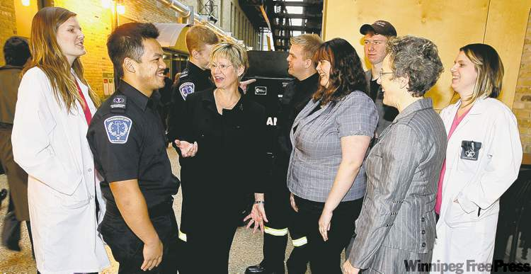 Education Minister Nancy Allan (centre) talks with Red River College students and RRC president Stephanie Forsyth (in grey suit, right) on Thursday.