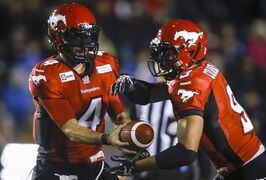 Calgary Stampeders quarterback Drew Tate, left, hands the ball off to teammate Jon Cornish during first quarter CFL football action against the B.C. Lions in Calgary, Saturday, Sept. 27, 2014. Cornish has won a pair of CFL monthly awards after putting up big numbers in September.THE CANADIAN PRESS/Jeff McIntosh