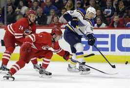 St. Louis Blues' Dmitrij Jaskin (23), of Russia, shoots the puck as Carolina Hurricanes' Ryan Murphy (7) and Brad Malone (24) defend during the first period of an NHL hockey game in Raleigh, N.C., Friday, Jan. 30, 2015. (AP Photo/Gerry Broome)