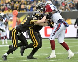Hamilton Tiger-Cats defenders Carig Butler (left) and Delvin Breaux (centre) team up to stop Montreal Alouettes quarterback Jonathan Crompton during first half action in the CFL Eastern Division final in Hamilton, Ont., on Sunday, Nov. 23, 2014. Every once in a while, Breaux walks out of a store only to be stopped when the anti-theft detection system goes off. THE CANADIAN PRESS/Nathan Denette