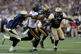 Winnipeg Blue Bombers' Maurice Leggett (31) can't stop Hamilton Tiger-Cats' Mossis Madu (26) as he jumps into the end zone for a touchdown during first half CFL football action at Investors Group Field in Winnipeg, Saturday.