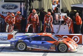 Driver Scott Dixon (02) in the DP Ford makes hit last pit stop for fuel before winning the IMSA 24 hour auto race at Daytona International Speedway, Sunday, Jan. 25, 2015, in Daytona Beach, Fla. (AP Photo/David Graham)