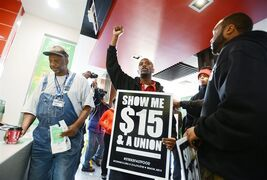 "FILE - In this Thursday, Dec. 4, 2014, file photo, a customer, left, stands at the counter as a group of protesters demonstrate inside the McDonald's restaurant on Northside Drive at Hanging Moss Road in Jackson, Miss. In 2014, fast-food workers continued their push to get consumers thinking about the other side of the Dollar Menu equation. The ""Fight for $15"