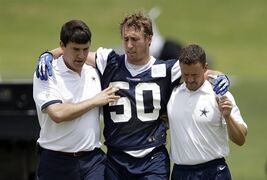 ADVANCE FOR WEEKEND EDITIONS, JULY 26-27 - FILE - In this May 27, 2014 file photo, Dallas Cowboys linebacker Sean Lee is helped off the field by head athletic trainer Jim Maurer, left, and associate athletic trainer Britt Brown, right, after suffering an unknown left leg injury during an NFL football organized team activity in Irving, Texas. With training camps starting up, team owners and fantasy football fans alike are holding their collective breath and praying to reach the regular season with their rosters intact. (AP Photo/Tony Gutierrez, File)