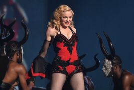 FILE - This Feb. 8, 2015 file photo shows Madonna performing at the 57th annual Grammy Awards in Los Angeles. The pop icon said in an interview Thursday, March 5, that being active saved her from serious injuries at the Brit Awards. The 56-year-old tumbled Feb. 25, during a live performance after her dancers tugged at her flowing cape, dragging her down three steps. Madonna said the cape had been tied too tightly at the neck, and after the performance, said she suffered whiplash. (Photo by John Shearer/Invision/AP)