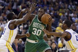 Boston Celtics' Brandon Bass (30) is guarded by Golden State Warriors' Draymond Green, left, and Harrison Barnes during the first half of an NBA basketball game Sunday, Jan. 25, 2015, in Oakland, Calif. (AP Photo/Ben Margot)