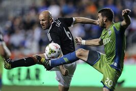 Union's Conor Casey, left, kicks the ball with Seattle Sounders FC's Zach Scott during the first half of the US Open Cup. at PPL Park in Chester, Pa., Tuesday, Sept.16, 2014. ( AP Photo / The Philadelphia Daily News, Steven M. Falk ) THE EVENING BULLETIN OUT, TV OUT; MAGS OUT; NO SALES