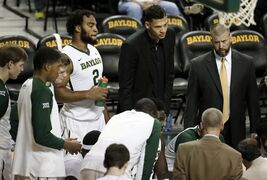 ADVANCE FOR WEEKEND EDITION, JAN. 31-FEB. 1 - In this photo taken Jan. 14, 2015, Baylor forward Rico Gathers (2), student assistant Isaiah Austin and strength coach, Charlie Melton, top right, listen to instructions in a team huddle during a time out from an NCAA college basketball game against Iowa State in Waco, Texas. These are not exactly the big basketball dreams once imagined by the 7-foot-1 Austin, the player with a prosthetic eye who only days before the draft last year was diagnosed with a rare genetic disorder that can affect his heart. He now works to make people aware of Marfan Syndrome, with a positive attitude he hopes will help others overcome their obstacles. (AP Photo/Tony Gutierrez)