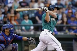 Seattle Mariners' Kyle Seager singles in a run as New York Mets catcher Travis d'Arnaud looks on in the first inning of a baseball game Monday, July 21, 2014, in Seattle. (AP Photo/Elaine Thompson)