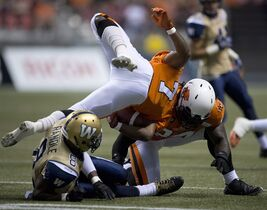 B.C. Lions' Tim Brown, centre, crashes into teammate Emmanuel Arceneaux as Winnipeg Blue Bombers' Chris Randele looks on during the first half of CFL football action in Vancouver, B.C., on Saturday Sept. 13, 2014. THE CANADIAN PRESS/Jonathan Hayward
