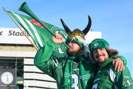 Saskatchewan Roughriders fans Jamie Hjlte (left) and Mike Brushun ham it up outside Mosaic Stadium before the Grey Cup game.