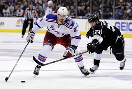 Los Angeles Kings right wing Dustin Brown, right, battles New York Rangers left wing Chris Kreider for the puck during the third period of Game 1 in the NHL Stanley Cup Final hockey series on Wednesday, June 4, 2014, in Los Angeles. Kreider and the New York Rangers agreed on a two-year deal shortly before going to arbitration. THE CANADIAN PRESS/AP/Jae C. Hong