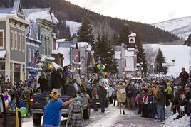 CORRECTS SPELLING OF BUD LITE TO BUD LIGHT - FILE - In this Feb. 24, 2009 file photo, a crowd gathers on Elk Avenue in Crested Butte, Colo., during a Mardi Gras parade celebration. Some people in normally laid back Crested Butte, are not up for a secretive Bud Light plan to paint their mountain town blue and turn it into a fantasy town for an ad campaign. The Denver Post reports the company has agreed to pay the town $250,000 to fence off its main street and bring in more than 1,000 revelers for the Sept. 5-7 event. (AP Photo/Nathan Bilow, File)