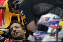 Red Bull driver Daniel Ricciardo of Australia talks with his team crew at the garage during the first practice session for the Malaysian Formula One Grand Prix at Sepang International Circuit in Sepang, Malaysia Friday, March 27, 2015. (AP Photo/Andy Wong)