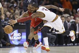 Cleveland Cavaliers' Kyrie Irving (2) and Toronto Raptors' Kyle Lowry (7) battle for a loose ball in the first quarter of an NBA basketball game Saturday, Nov. 22, 2014, in Cleveland. (AP Photo/Tony Dejak)