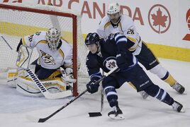 Winnipeg Jets' Mark Scheifele (55) goes for the wrap-around against Nashville Predators' goaltender Carter Hutton (30) and Paul Gaustad (28) during the third period of Tuesday's game. The Predators won 4-3.