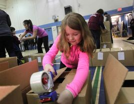 Nine-year-old Julia Lukowich seals Christmas hampers with more than 200 other volunteers at R.B. Russell School Saturday.