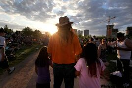 Residential school survivor Martin Tuesday of Sioux Lookout, Ont., holds his grandchildren close while attending the TRC concert Wednesday evening.