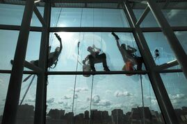 Ruth Bonneville / Winnipeg Free Press  Highrise window-washers with Picture Perfect Window Cleaning wash the glass on the Canadian Museum for Human Rights on Tuesday in preparation for the grand opening, which is less than two months away.