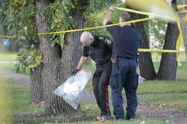 Police collect evidence Sunday at 98 Hill St. in St. Boniface where a woman who was stabbed later died of her wounds.